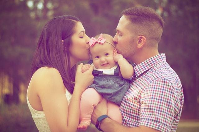 Muž a žena bozkávajúci dieťa