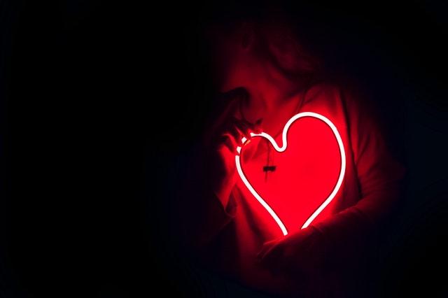 Žena v tme drží pri tele svietiace srdce.jpg
