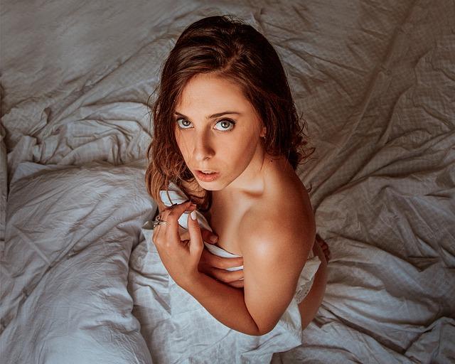 Žena sedí na posteli zabalená v plachte a tvári sa prekvapene.jpg
