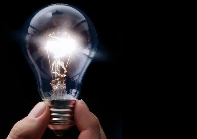 Ruka drží svietiacu žiarovku.jpg
