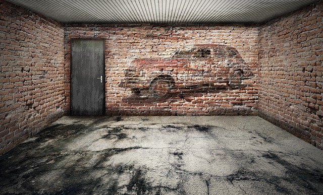 Garáž s tehlovou stenou, na ktorej je namaľované auto