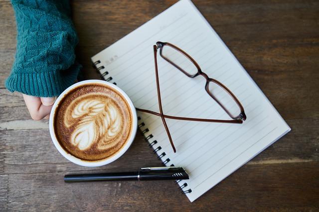 Notes, okuliare a žena drží v ruke šálku s kávou